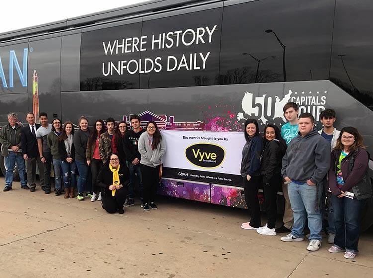 Vyve employees and Shawnee students pose with a Vyve banner outside the CSPAN 50 Capitals Tour bus