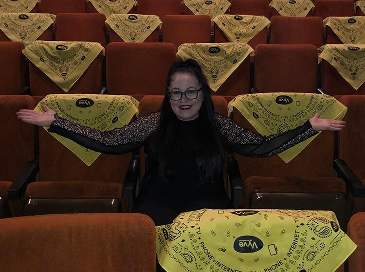 Vyve employee poses with Vyve branded bandanas in a theatre