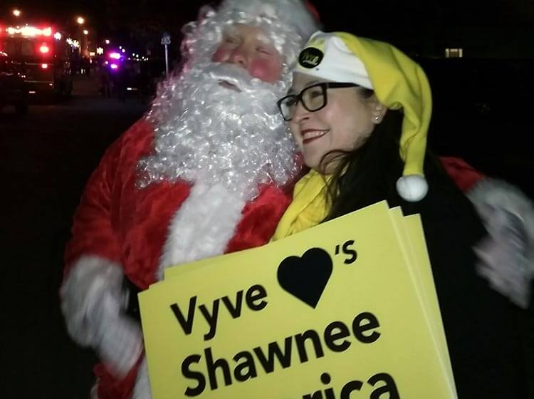 Vyve employee poses with Santa during the Shawnee Christmas Parade