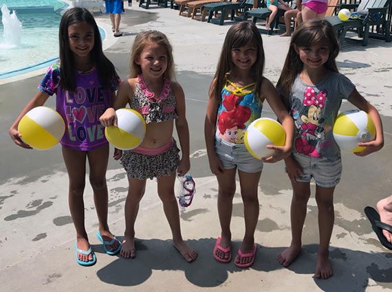 Children posing for a picture with Vyve beach balls at Shawnee Splash!
